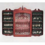 Large quantity of souvenir spoons intwo display shelves and a display case and various loose spoons