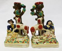 Pair of reproduction Staffordshire vases, the bases of each modelled with a seated figure surrounded
