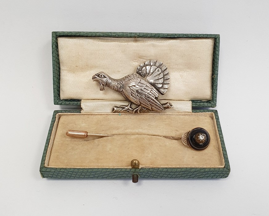 Gold-coloured stickpin, the banded onyx head set with a central diamond and a silver broochof a