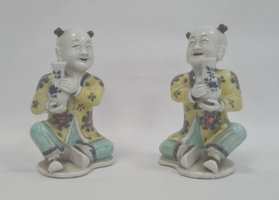 Pair of Chinese porcelain seated figures, laughing boys, each holding a blue and white vase, 16cm