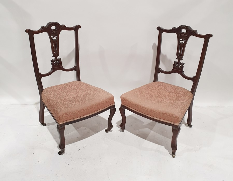 Pair of Edwardian low bedroom chairs with carved and pierced backsplat, pink upholstered seat,