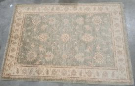 Modern pale green ground Eastern-style rugwith foliate decoration to the central field, cream