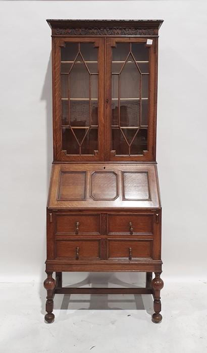 20th century oak bureau bookcase, the moulded pediment above two astragal glazed doors enclosing
