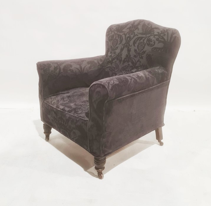 Late Victorian armchair withblack loose covers, on turned front legs to brown china castors