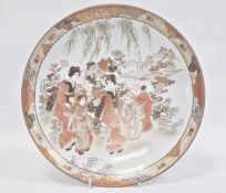 Japanese Kutani porcelain shallow dish, circular and decorated with figures beside a lake in iron