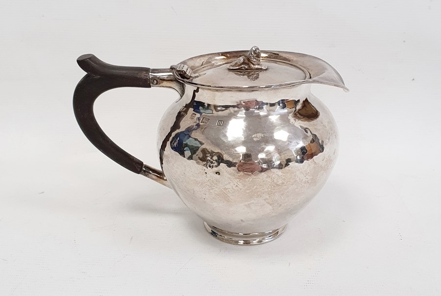 Silver covered jugby A E Jones, London 1911 of circular form with hammered finish, the hinged cover