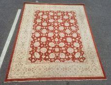 Modern Eastern-style rug, red ground with cream allover foliate decoration, cream ground border,