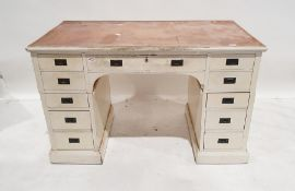 Early 20th century white painted pedestal desk, with campaign-style handles, 11 assorted drawers, on