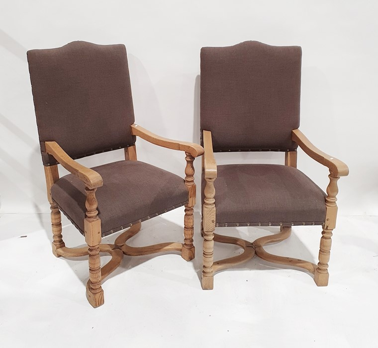 Pair of modern oak-framed armchairwith brown upholstered seats and backs, wavy X-shaped stretchered