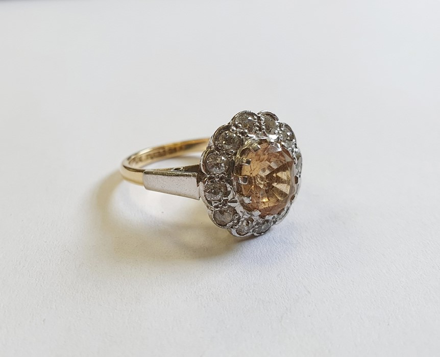 18ct gold, champagne topaz and diamond cluster ring, the centre oval mixed cut topaz surrounded by