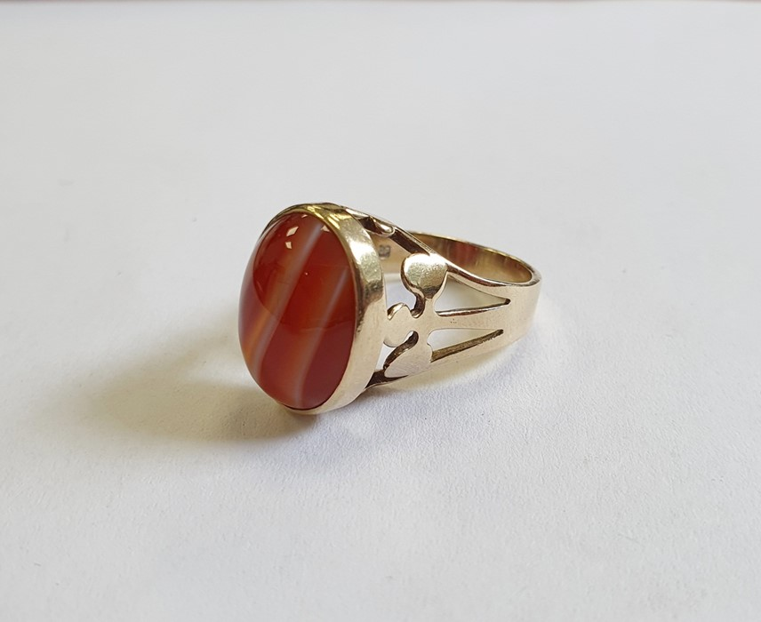 9ct gold ringset with a banded agate cabochon and with pierced trefoil shoulders, finger size M 1/