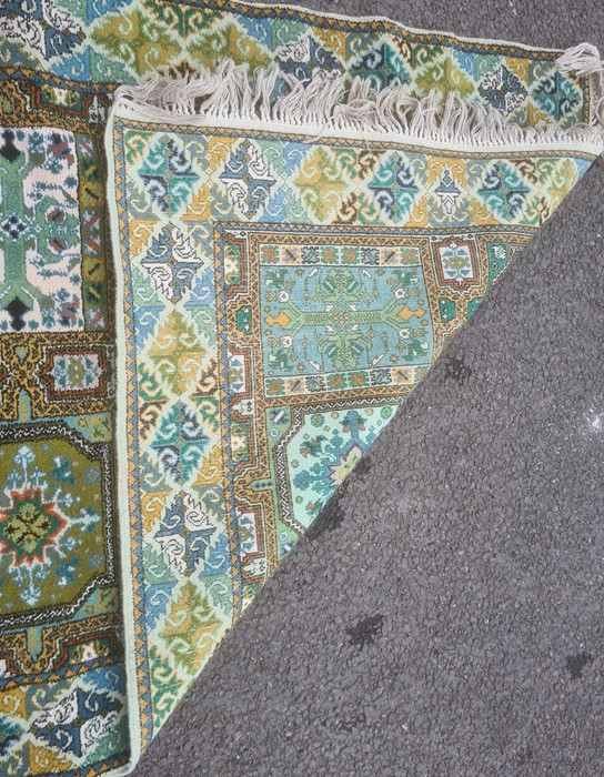 Modern green ground rug, the central field with ten panels in blues, greens and yellows, 120cm x - Image 2 of 2
