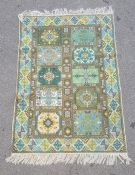 Modern green ground rug, the central field with ten panels in blues, greens and yellows, 120cm x