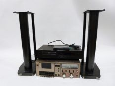 Rotel DVD player and a Teac stereo cassette deck and a pair of speaker stands