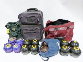 Box of assorted bowling trophies and a set of Thomas Taylor bowls in carrying bag and two other sets