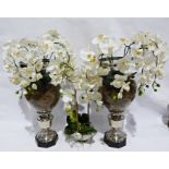 Two large silver coloured metal and glass vases with faux orchids displayed, and a glass bowl of