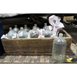 Ten vintage bottles held within a wooden carrier, probably decorative purposes only, with deliberate