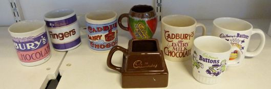 Two boxes of assorted mugs advertising Cadbury's chocolate to include Dairy Milk, Chocolate Buttons,