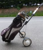 Golf clubs within a golf caddy on wheels and the golf clubs seem to be mainly by Tanaka