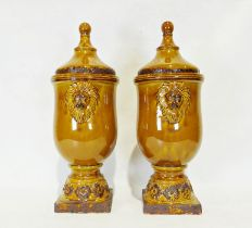 Pair of modern treacle glazed ceramic urn-shaped lidded vaseswith applied lion decoration (2)