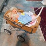 Vintage dolls pramand contents of three composition dolls and assorted dolls clothes and