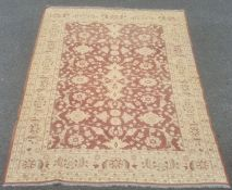 Large kilim the central field decorated with cream flowerheads on a brown ground within a wide