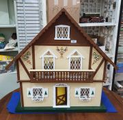 Modern wooden doll's housein the form of a chalet, with painted decoration