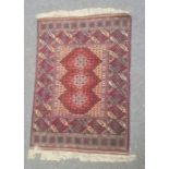 Modern rug, the central field with three medallions within a border of square panels, 164cm x
