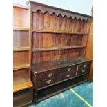 Early 20th century stained pine dresser, the moulded cornice above open shelves, the base with six