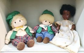 Two wind-up musical dolls with green hats and tartan outfits and an Armand Marseille black doll, the