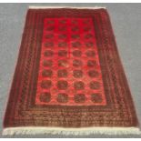 Modern Afghan rug, the central field with elephant foot guls on a red ground with multiple