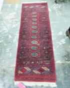 Eastern style red ground rug with ten elephant foot gul pattern in centre, with geometric border and