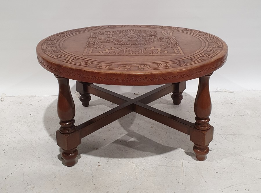Circular coffee tablewith brown leather top with aztec design, on turned and block supports,
