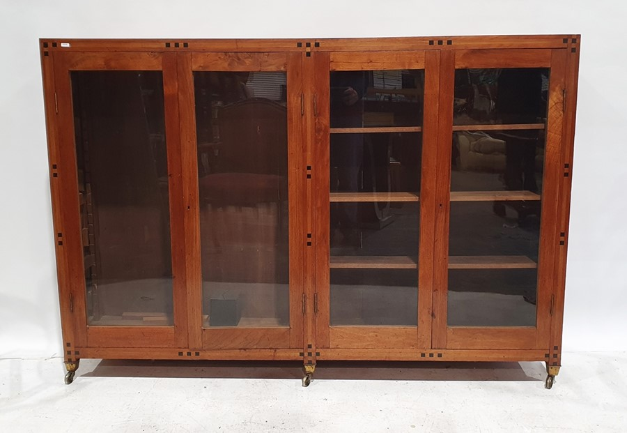 20th century mahogany inlaid bookcasewith four glazed doors enclosing shelves, all raised on
