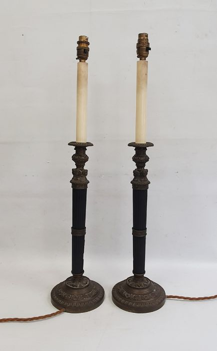 Pair of table lampswith fluted black composite stems and bronze-effect mounts, decorated with