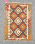 Maimana kilim rug decorated with lozenges in orange and blue on a brown ground, 113cm x 81cm.