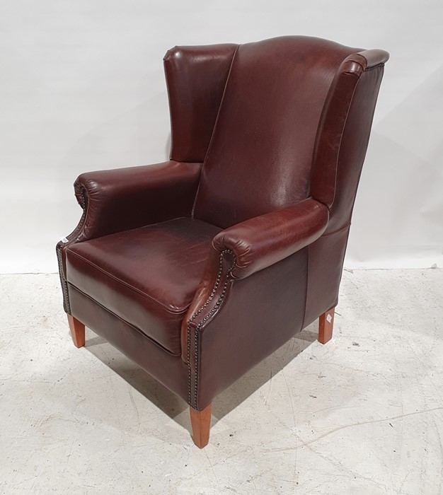 20th century brown leather wing-back office armchairon tapering supports