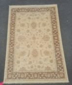 Modern rug, the central field decorated with stylised flowerheads on a cream ground, within a