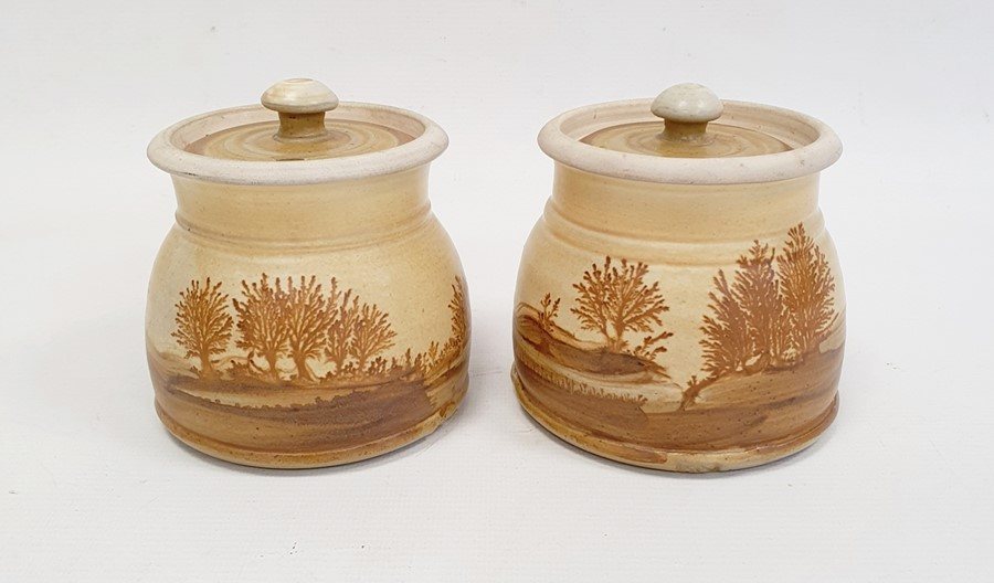 """Pair of Rupert Andrews """"Mocha"""" ware lidded preserve jars decorated with country landscapes,"""