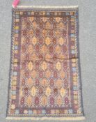 Baluchi rug, the central field decorated with brown lozenges within blue borders and within a floral