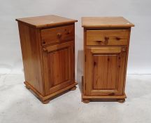 Pair of 20th century pine bedside tableswith single drawers above cupboard doors, on squat bun