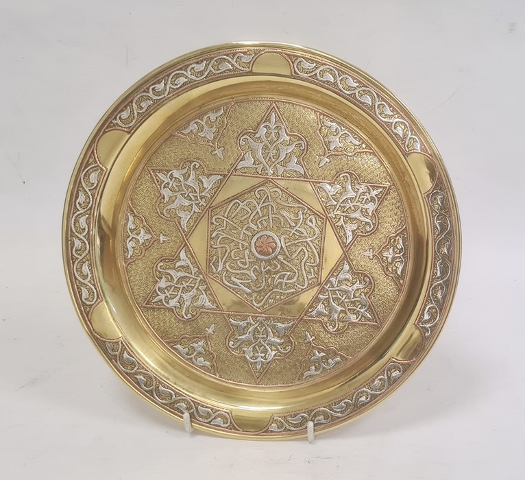 Middle Eastern brass dishof circular form with inlaid copper and silvered decoration, 24.5cm