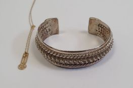Gold coloured pendant on chain, 0.5g approx. and asilver coloured bangle (2)