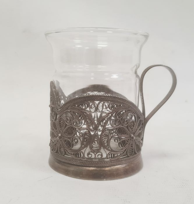 Silver-coloured metal filigree cup holder, flower decorated, with marks to base and a glass cup(not