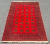 Modern Afghan rug, the central field with elephant's foot guls on a red ground with multiple