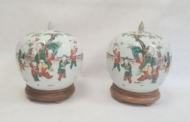 Pair of 19th century Chinese jars and coversof spherical form, decorated with continuous scenes