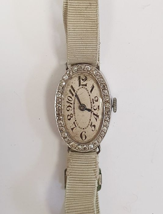 A 1920s platinum and diamond lady's wristwatch on fabric strap, oval with Arabic numerals and an