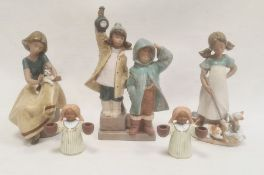 Lladro model of a seated girl with a cat on her lap, 21cm high, another Lladro model of two children