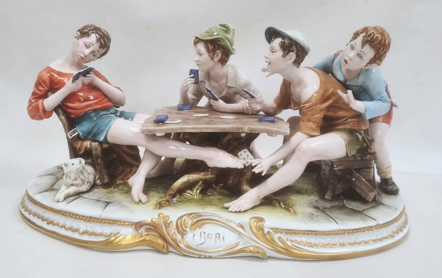 Ciche porcelain figural groupof boys seated at a table playing cards, the oval base with gilt