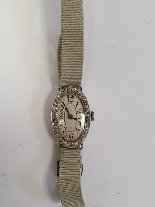A 1920s platinum and diamond lady's wristwatch on fabric strap, oval with Arabic numerals and an - Image 2 of 10